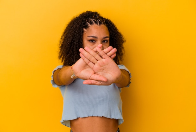 Młoda afroamerykanka odizolowana na żółtym tle wykonująca gest odmowy
