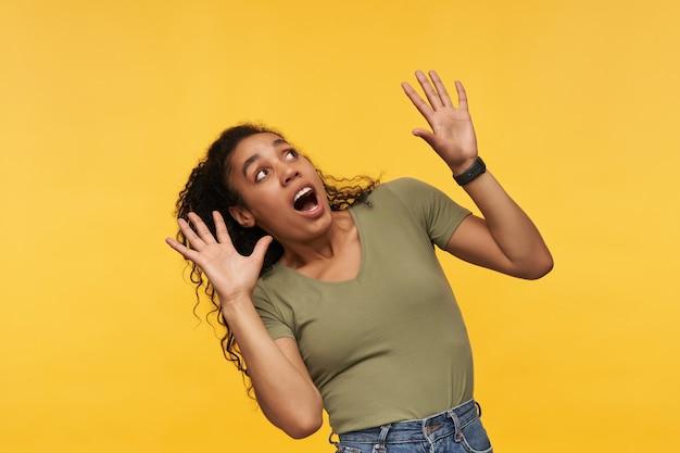 Młoda afroamerykanka, patrząca w górę z przerażonym wyrazem twarzy