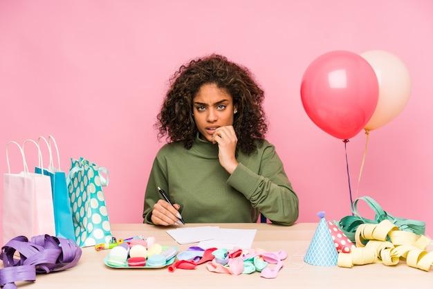 Młoda afroamerykanka planująca urodziny obgryza paznokcie, jest zdenerwowana i bardzo niespokojna.