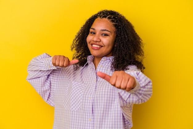 Młoda afroamerykanka podnosząca kciuki do góry, uśmiechnięta i pewna siebie.