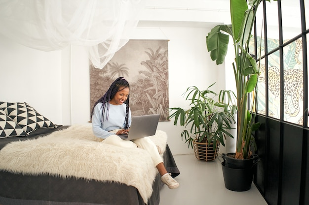 Młoda afroamerykanka pracuje zdalnie z domu w sypialni, siedząc na łóżku za pomocą laptopa