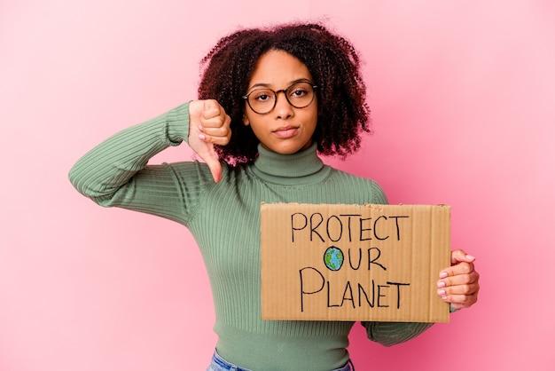 Młoda afroamerykanka rasy mieszanej kobieta trzyma karton chroni naszą planetę, pokazując gest niechęci, kciuk w dół. pojęcie sporu.