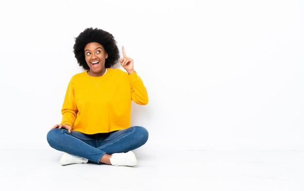 Młoda afroamerykanka siedząca na podłodze, która zdaje sobie sprawę z rozwiązania, podnosząc palec w górę