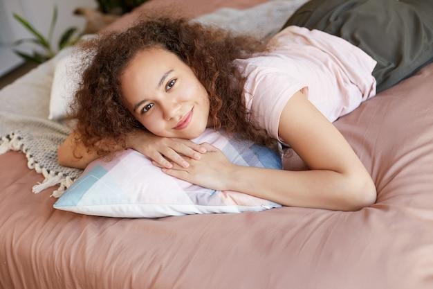 Młoda afroamerykanka śliczna, kręcona dama na łóżku, wygląda na szczęśliwą, cieszy się słonecznym dniem w domu i się uśmiecha.