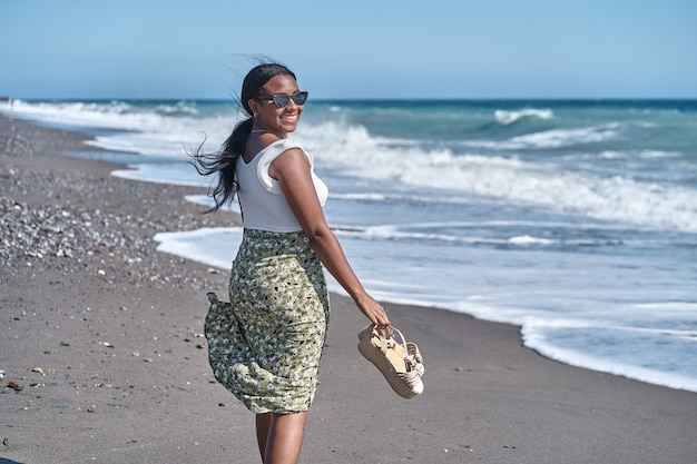 Młoda afroamerykanka spacerująca brzegiem plaży z sandałami w dłoni