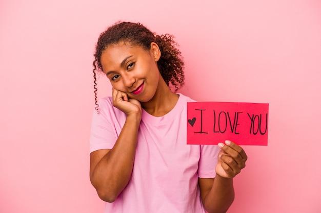Młoda afroamerykanka trzyma afisz kocham cię na białym tle na różowym tle