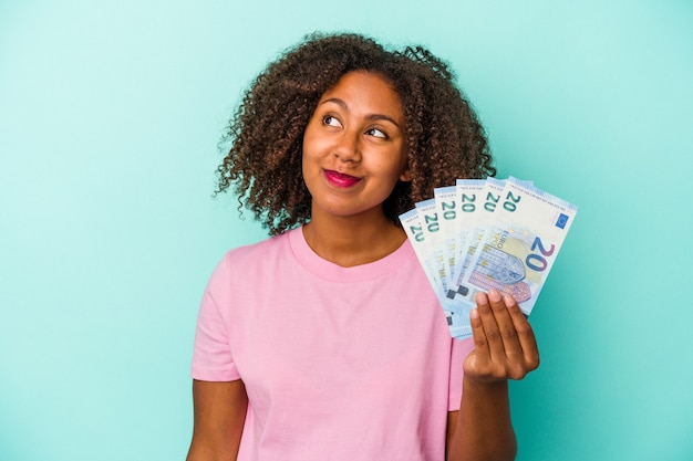 Młoda afroamerykanka trzyma banknoty euro na białym tle na niebieskim tle, marząc o osiągnięciu celów i celów