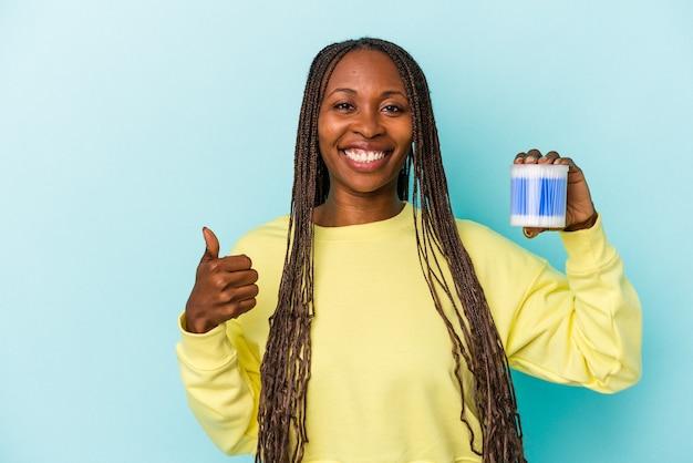 Młoda afroamerykanka trzyma bawełniane byki na białym tle na tle pąków, uśmiechając się i podnosząc kciuk w górę