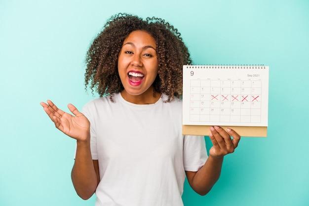 Młoda afroamerykanka trzyma kalendarz na białym tle na niebieskim tle otrzymując miłą niespodziankę, podekscytowana i podnosząc ręce.