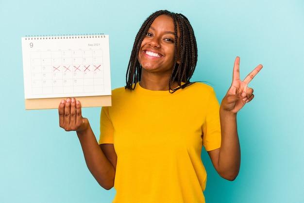 Młoda afroamerykanka trzyma kalendarz na białym tle na niebieskim tle radosna i beztroska pokazująca palcami symbol pokoju.