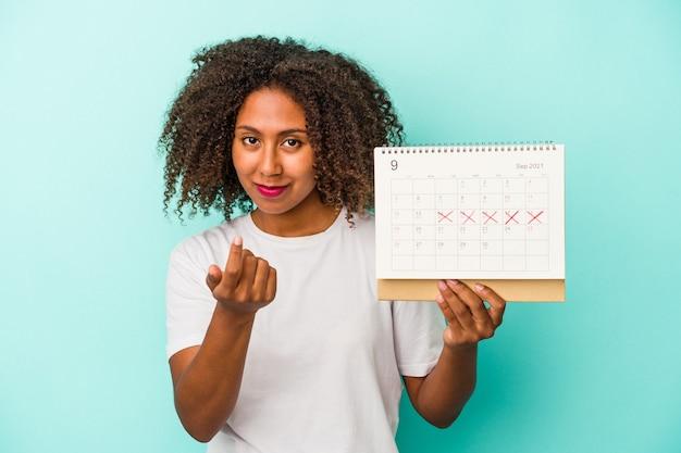 Młoda afroamerykanka trzyma kalendarz na białym tle na niebieskim tle, wskazując palcem na ciebie, jakby zapraszając podejść bliżej.
