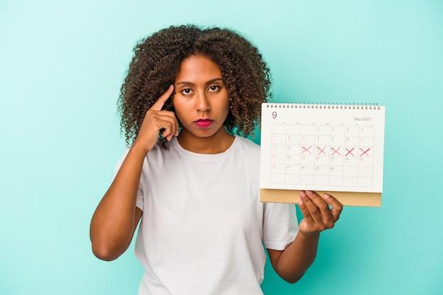 Młoda afroamerykanka trzyma kalendarz na białym tle na niebieskim tle wskazując świątynię palcem, myśląc, skupiona na zadaniu.