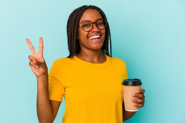 Młoda afroamerykanka trzyma kawę na wynos na białym tle na niebieskim tle radosna i beztroska pokazująca palcami symbol pokoju.