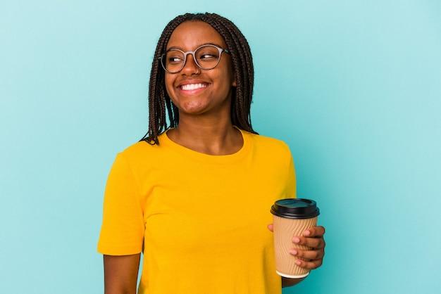 Młoda afroamerykanka trzymająca kawę na wynos na białym tle na niebieskim tle wygląda na uśmiechniętą, wesołą i przyjemną.