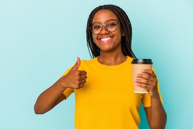 Młoda afroamerykanka trzymająca kawę na wynos na niebieskim tle, uśmiechnięta i unosząca kciuk w górę