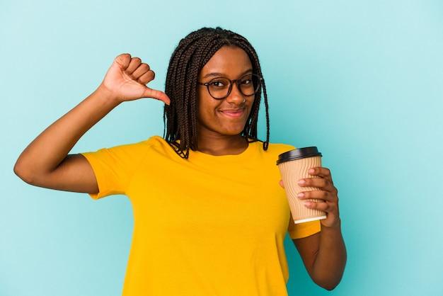 Młoda afroamerykanka trzymająca kawę na wynos odizolowana na niebieskim tle czuje się dumna i pewna siebie, przykład do naśladowania.