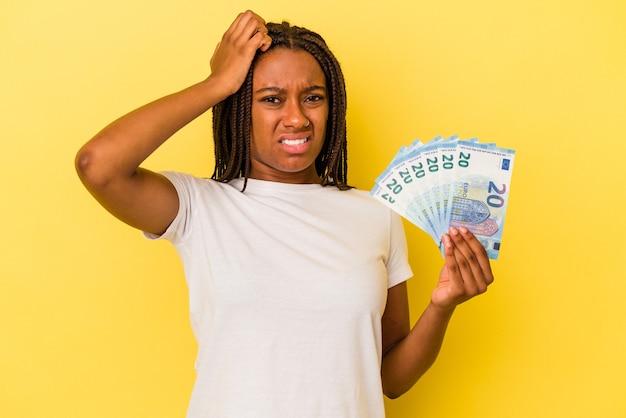Młoda afroamerykanka trzymająca rachunki na białym tle na żółtym tle będąc zszokowana, przypomniała sobie ważne spotkanie.