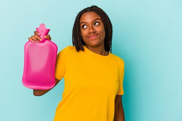 Młoda afroamerykanka trzymająca worek gorącej wody na białym tle na niebieskim tle marząca o osiągnięciu celów i celów