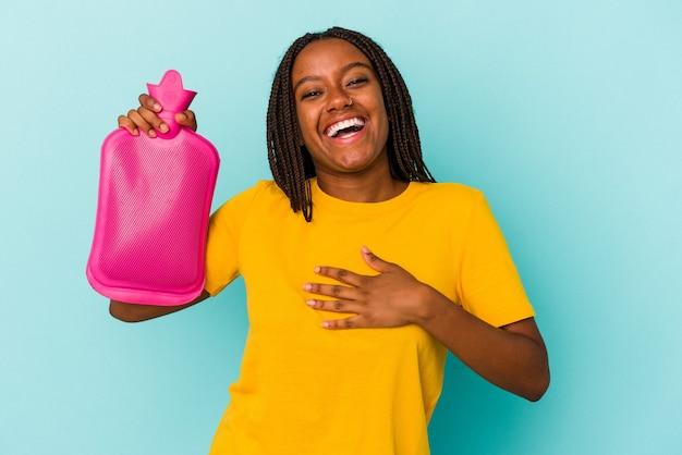 Młoda afroamerykanka trzymająca worek gorącej wody na białym tle na niebieskim tle śmieje się głośno trzymając rękę na klatce piersiowej.