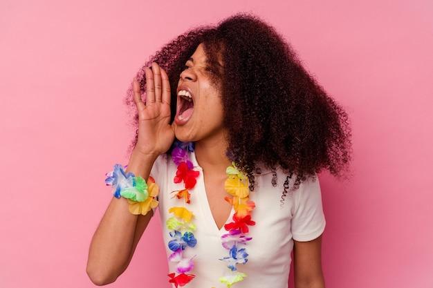 Młoda afroamerykanka ubrana w hawajskie rzeczy krzyczy i trzyma dłoń w pobliżu otwartych ust.