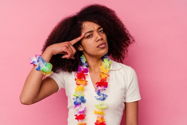 Młoda afroamerykanka ubrana w hawajskie rzeczy wskazuje świątynię palcem, myśli, skupiona na zadaniu.
