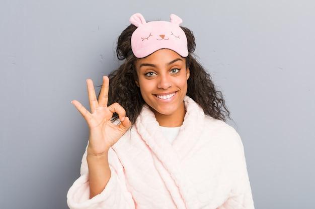 Młoda afroamerykanka ubrana w piżamę i maskę do spania, wesoła i pewna siebie, pokazuje ok gest.