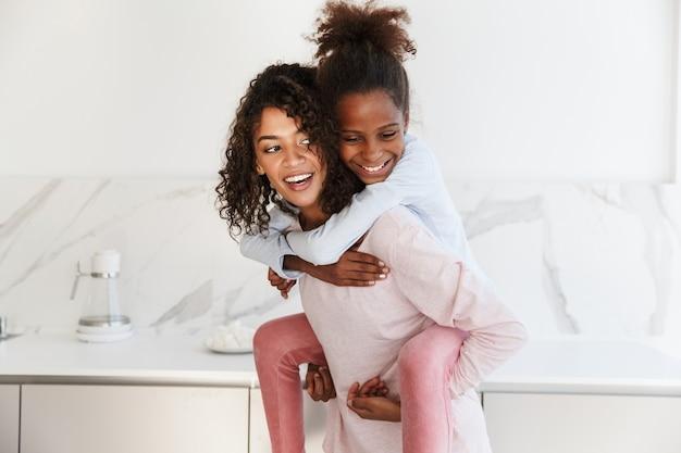 Młoda afroamerykanka uśmiecha się i piggybacking swoją małą córeczkę w domu