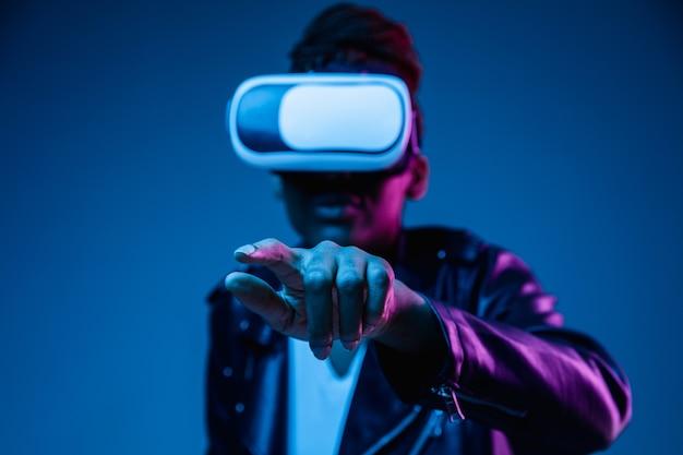 Młoda afroamerykanka używa okularów vr w neonowym świetle