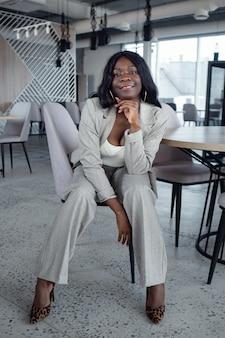 Młoda afroamerykanka w garniturze siedzi na krześle