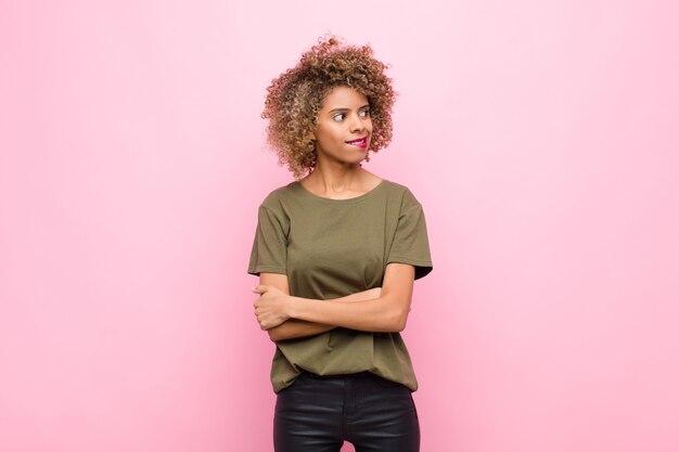 Młoda afroamerykanka wątpiąca lub myśląca, przygryzająca wargę i czująca się niepewnie i nerwowo, chcąca skopiować przestrzeń z boku na różowej ścianie