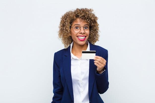 Młoda afroamerykanka wyglądająca na szczęśliwą i przyjemnie zaskoczoną, podekscytowana zafascynowaną i zszokowaną miną z kartą kredytową