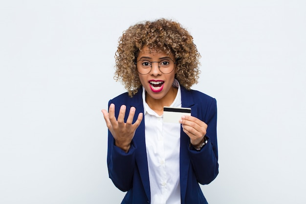 Młoda afroamerykanka wyglądająca na zdesperowaną i sfrustrowaną, zestresowaną, nieszczęśliwą i zirytowaną, krzyczącą i krzyczącą z kartą kredytową
