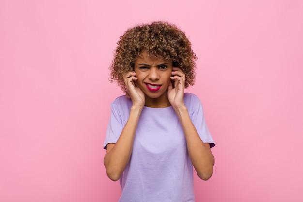 Młoda afroamerykanka, wyglądająca na złą, zestresowaną i zirytowaną, zakrywającą uszy ogłuszającym hałasem, dźwiękiem lub głośną muzyką na różowej ścianie