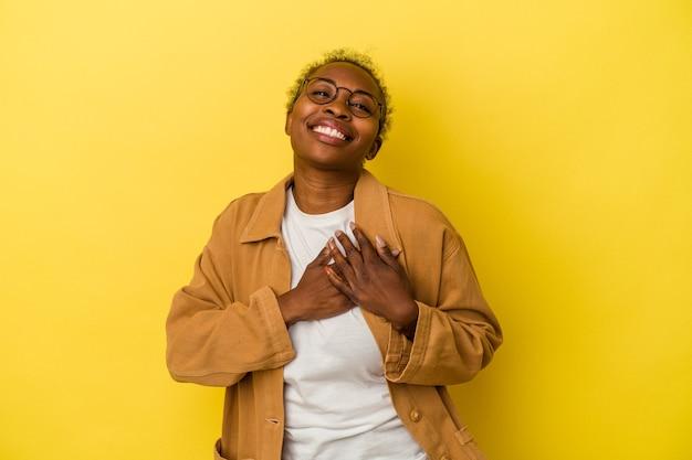 Młoda afroamerykanka wyizolowana na żółtym tle ma przyjazny wyraz, przyciskając dłoń do klatki piersiowej. koncepcja miłości.