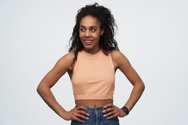 Młoda afroamerykanka z fryzurą w stylu afro, trzyma rękę na biodrach, uśmiecha się szeroko i odwraca wzrok na miejsce