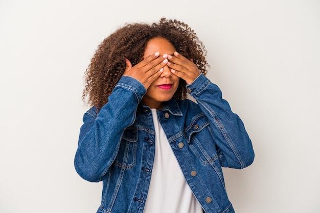 Młoda afroamerykanka z kręconymi włosami na białym tle boi się zasłaniając oczy rękami.