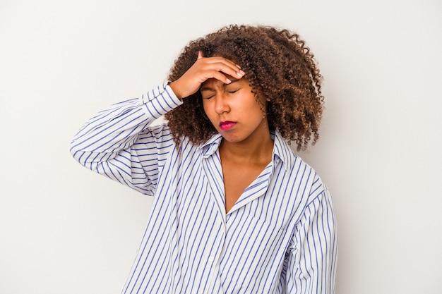 Młoda afroamerykanka z kręconymi włosami na białym tle dotyka świątyń i ma ból głowy.