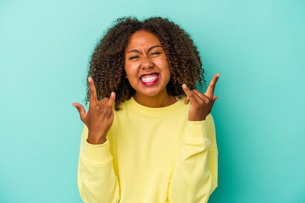 Młoda afroamerykanka z kręconymi włosami na białym tle na niebieskim tle pokazujący gest rogów jako koncepcja rewolucji.