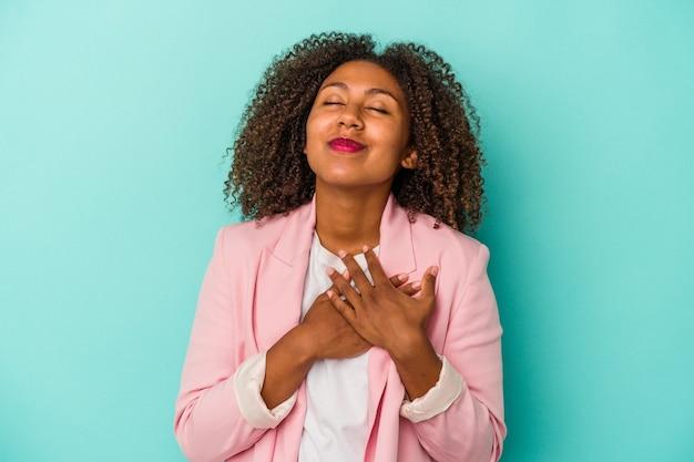 Młoda afroamerykanka z kręconymi włosami na niebieskim tle ma przyjazny wyraz, przyciskając dłoń do klatki piersiowej. koncepcja miłości.