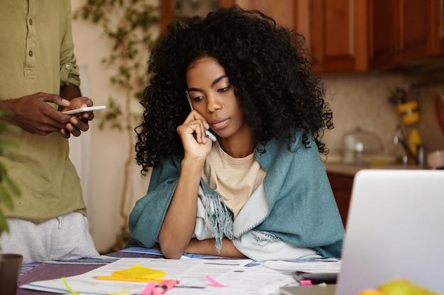 Młoda afroamerykanka z kręconymi włosami wyglądająca na zmartwioną pracującą nad finansami w kuchni, siedząca przy stole z laptopem i papierami, rozmawiająca przez telefon komórkowy z bankiem informująca o zadłużeniu kredytu
