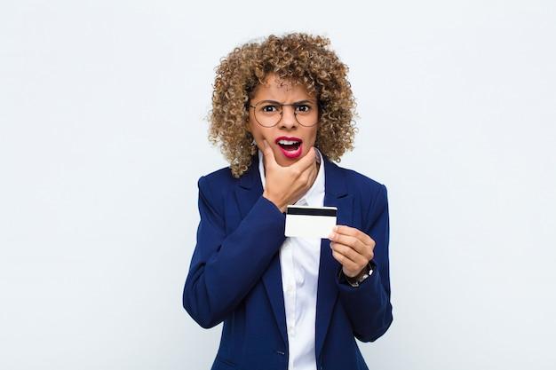 Młoda afroamerykanka z szeroko otwartymi ustami i oczami i dłonią na brodzie, nieprzyjemnie zszokowana, mówiąc co lub wow z kartą kredytową