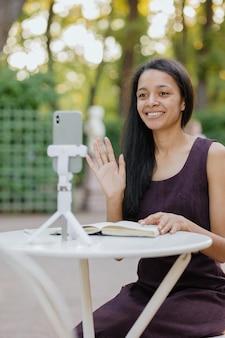 Młoda afroamerykanka z tysiąclecia ogląda webinarium lub transmisję na żywo ze swojego smartfona i