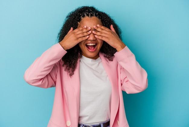 Młoda afroamerykanka zakrywa oczy rękami, uśmiecha się szeroko, czekając na niespodziankę.