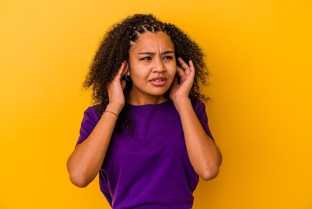 Młoda afroamerykanka zakrywająca uszy palcami, zestresowana i zdesperowana głośnym otoczeniem.