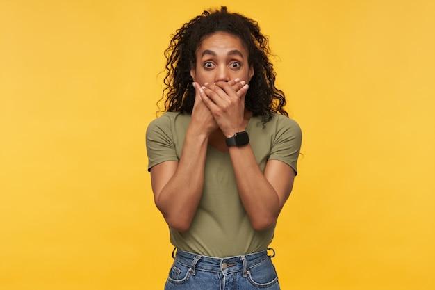 Młoda afroamerykanka zamknęła usta rękami, ma szeroko otwarte oczy eyes