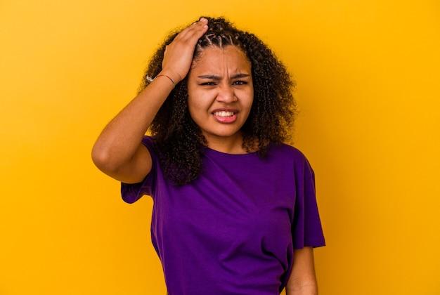 Młoda afroamerykanka zapomina o czymś, klepie dłonią w czoło i zamyka oczy.