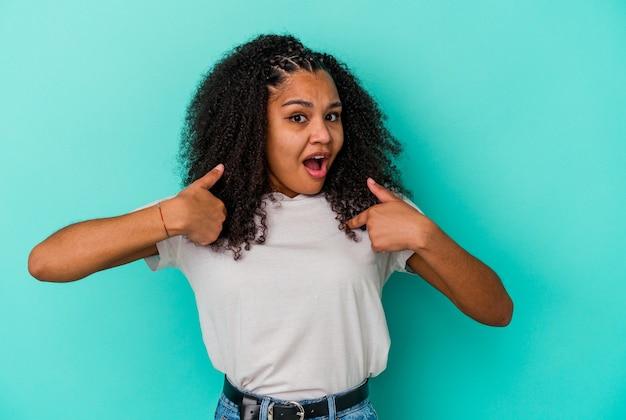 Młoda afroamerykanka zaskoczona, wskazując palcem, uśmiechając się szeroko.