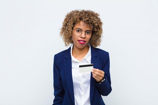 Młoda afroamerykanka zdziwiona i zdezorientowana, z głupim, oszołomionym wyrazem twarzy, patrząc na coś nieoczekiwanego za pomocą karty kredytowej