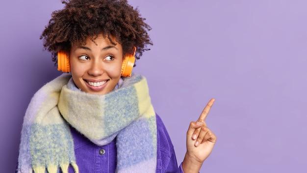 Młoda afroamerykanka ze słuchawkami, nosi ciepły szalik wokół szyi, czuje się szczęśliwa, wskazując miejsce na kopię