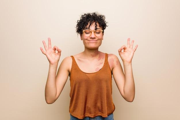 Młoda afroamerykanka ze znakiem urodzenia skóry relaksuje się po ciężkim dniu pracy, wykonuje jogę.